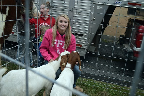 Carly Crofcheck spends some time with the boar goats in the petting zoo at Farm City Days.