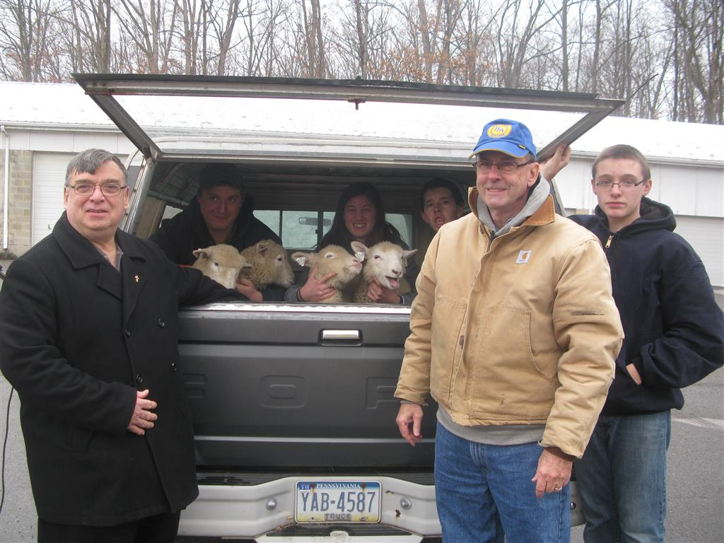 In December, Sam Hayes, Jr. (blue hat) took Charles Beard and Shaye Loose to get three ewes and one ram for the student to raise for the Lamb to Bank project.  Reverend Rother (long black coat) from the Tyrone Food Bank was on hand for the arrival of the lambs to the school and interviews with the local newspaper and radio station.  Nick Beard (far right) and David Conrad (in truck on right) were also on hand for the interviews and answered questions about why they wanted to help raise the lambs.  The lambs were raised until the end of March and the proceeds of $700 were donated to the Food Bank in time for them to purchase Easter Hams for families in need.
