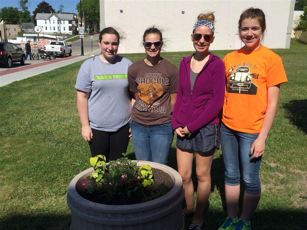 """FFA members Kelley Braun, Alicia Braun, Shania Abler, and Alexis Luedtke stood next to one of the planters that they helped to plant with some of our local master gardeners. While planting, members learned how to successfully utilize """"thrillers"""", """"fillers"""", and """"spillers"""" to end up with an attractive product."""