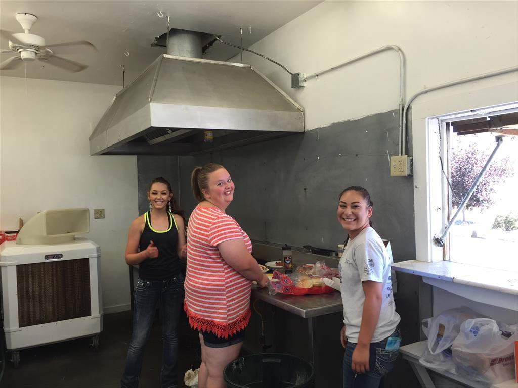 In this picture Kyley, Nora, and Natalie are cooking hamburgers and preparing them during the district rodeo.  We did this activity to earn money for National Convention.
