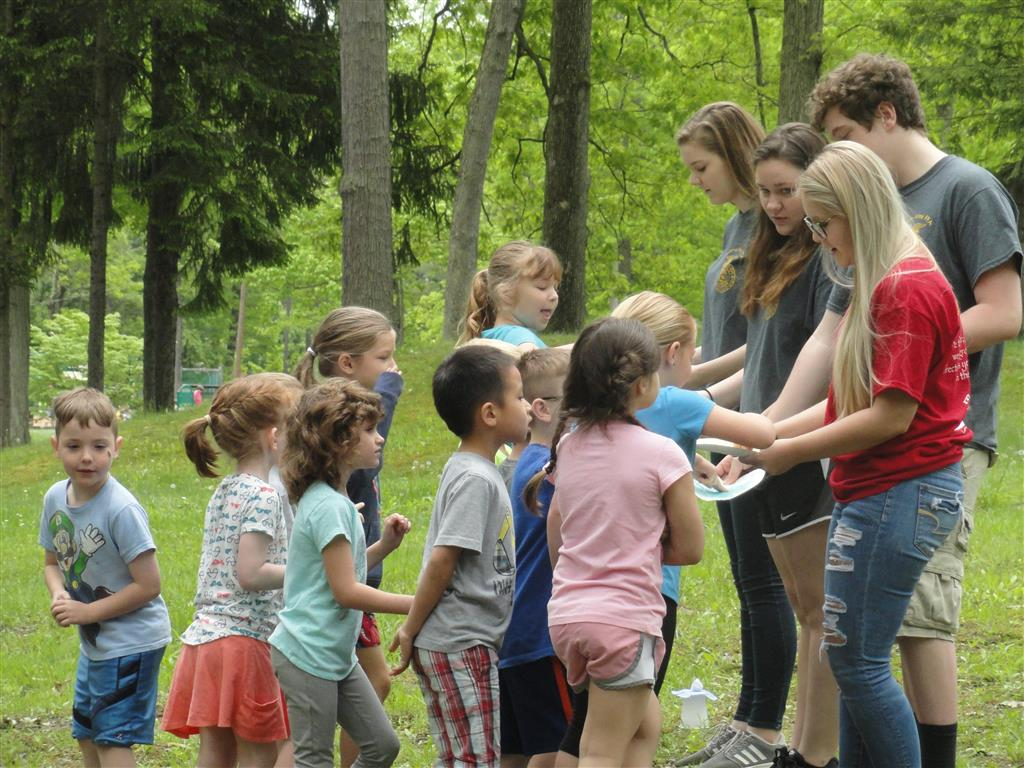 All 155 kindergarten students from the school district, along with their teachers and chaperones attended the 4 interactive stations. 10 lead teachers wrote and prepared the lesson plans for the stations, while an additional 18 members assisted the lead teachers. The Busy Bee pollination game (pictured) was a popular game.  Members created other activities when teachers decided to keep the students at the stations longer than scheduled - Bee freeze tag; hunting for decomposer (pill bugs another favorite); identify a sugar maple tree and explain how maple syrup was made for Tyler