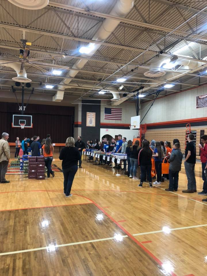The meal bagging is set up in the high school gym with two assembly lines and all of the extra food placed down the center. FFA member