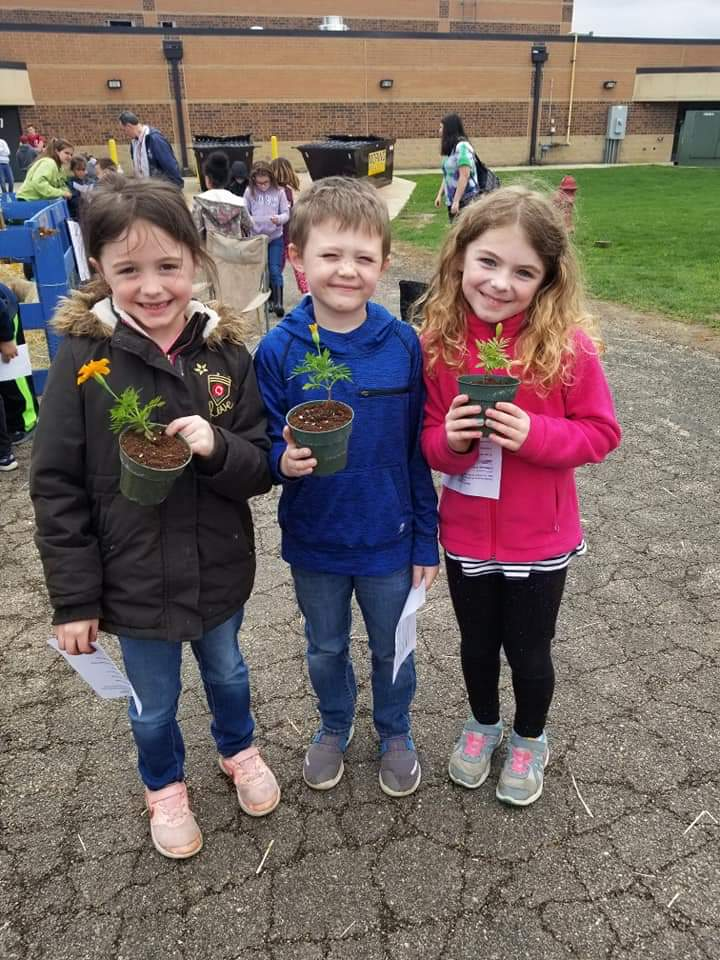 Students holding marigold flowers they transplanted to give to there moms for this mothers day!