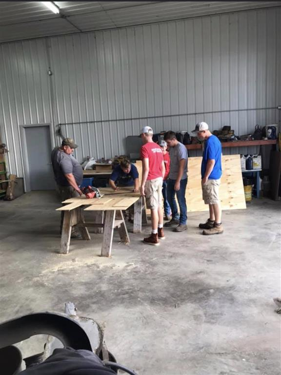 This photo has Ron Moser, Garret Moser, Adam Glendenning, Nolan Thomas, and Alummni Member Austin Strite, at Garret Mosers shop. FFA Members are cutting out the letters FFA for the Autimon Prade.The 3 letters will go across 3 side by sides.
